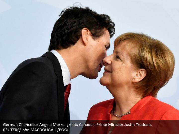 German Chancellor Angela Merkel greets Canada's Prime Minister Justin Trudeau. REUTERS/John MACDOUGALL/POOL