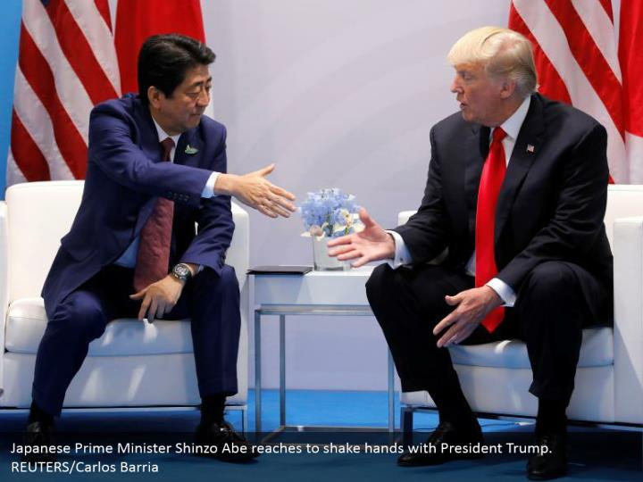 Japanese Prime Minister Shinzo Abe reaches to shake hands with President Trump. REUTERS/Carlos Barria