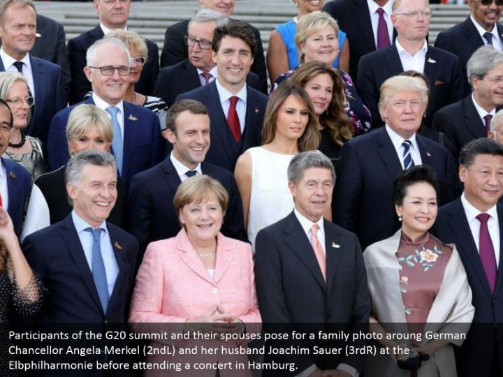 Participants of the G20 summit and their spouses pose for a family photo aroung German Chancellor Angela Merkel (2ndL) and her husband Joachim Sauer (3rdR) at the Elbphilharmonie before attending a concert in Hamburg.