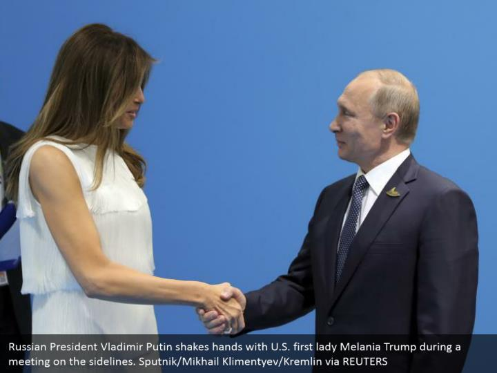 Russian President Vladimir Putin shakes hands with U.S. first lady Melania Trump during a meeting on the sidelines. Sputnik/Mikhail Klimentyev/Kremlin via REUTERS