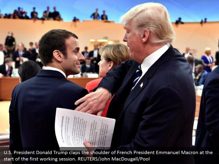 U.S. President Donald Trump claps the shoulder of French President Emmanuel Macron at the start of the first working session. REUTERS/John MacDougall/Pool