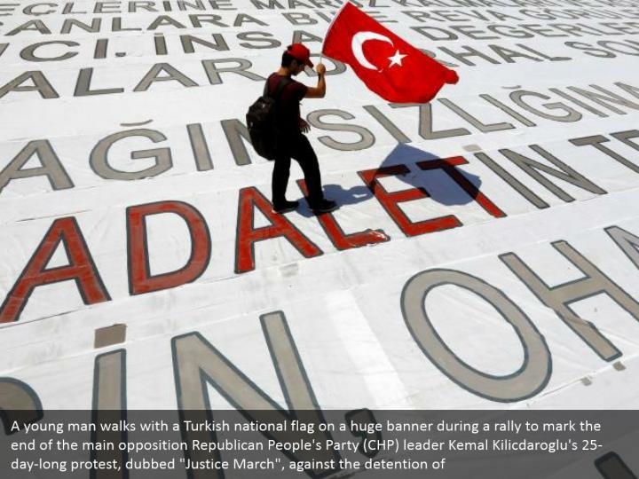 """A young man walks with a Turkish national flag on a huge banner during a rally to mark the end of the main opposition Republican People's Party (CHP) leader Kemal Kilicdaroglu's 25-day-long protest, dubbed """"Justice March"""", against the detention of"""