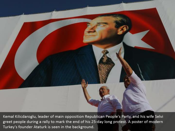 Kemal Kilicdaroglu, leader of main opposition Republican People's Party, and his wife Selvi greet people during a rally to mark the end of his 25-day long protest. A poster of modern Turkey's founder Ataturk is seen in the background.