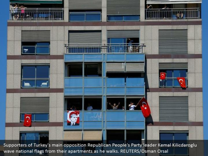 Supporters of Turkey's main opposition Republican People's Party leader Kemal Kilicdaroglu wave national flags from their apartments as he walks. REUTERS/Osman Orsal