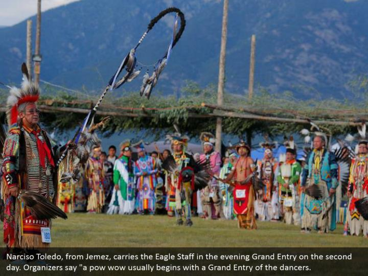 """Narciso Toledo, from Jemez, carries the Eagle Staff in the evening Grand Entry on the second day. Organizers say """"a pow wow usually begins with a Grand Entry of the dancers."""