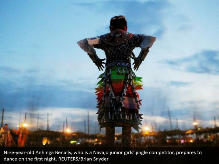 Nine-year-old Anhinga Benally, who is a Navajo junior girls' jingle competitor, prepares to dance on the first night. REUTERS/Brian Snyder