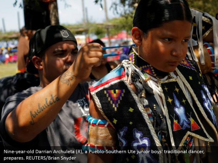 Nine-year-old Darrian Archuleta (R), a Pueblo-Southern Ute junior boys' traditional dancer, prepares. REUTERS/Brian Snyder