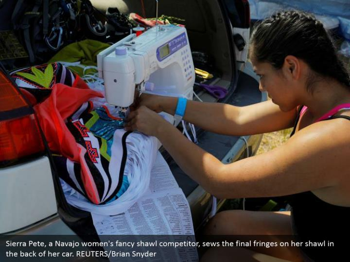 Sierra Pete, a Navajo women's fancy shawl competitor, sews the final fringes on her shawl in the back of her car. REUTERS/Brian Snyder