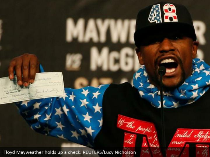 Floyd Mayweather holds up a check. REUTERS/Lucy Nicholson