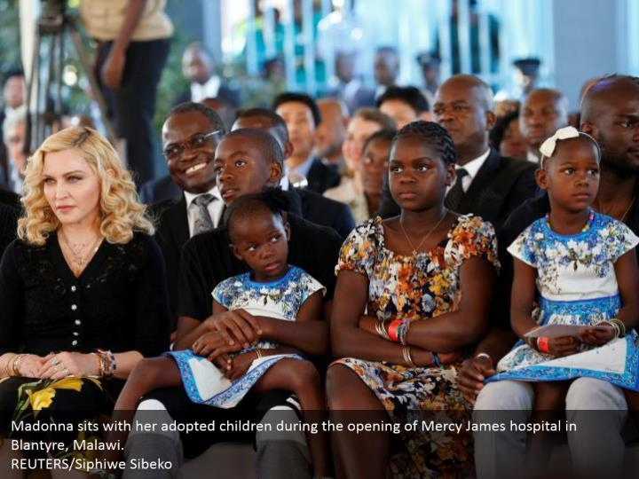 Madonna sits with her adopted children during the opening of Mercy James hospital in Blantyre, Malawi.  REUTERS/Siphiwe Sibeko