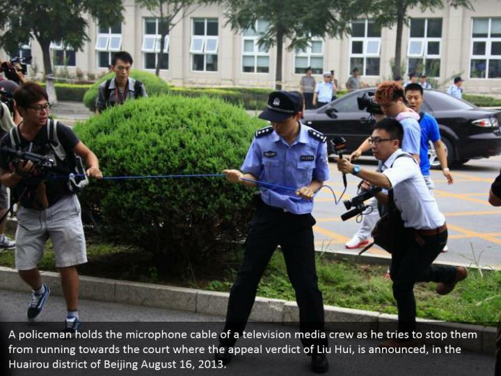 A policeman holds the microphone cable of a television media crew as he tries to stop them from running towards the court where the appeal verdict of Liu Hui, is announced, in the Huairou district of Beijing August 16, 2013.