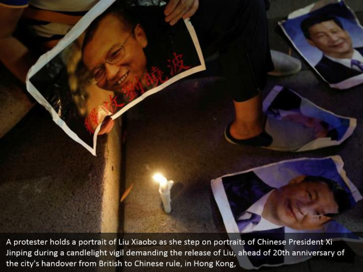 A protester holds a portrait of Liu Xiaobo as she step on portraits of Chinese President Xi Jinping during a candlelight vigil demanding the release of Liu, ahead of 20th anniversary of the city's handover from British to Chinese rule, in Hong Kong,
