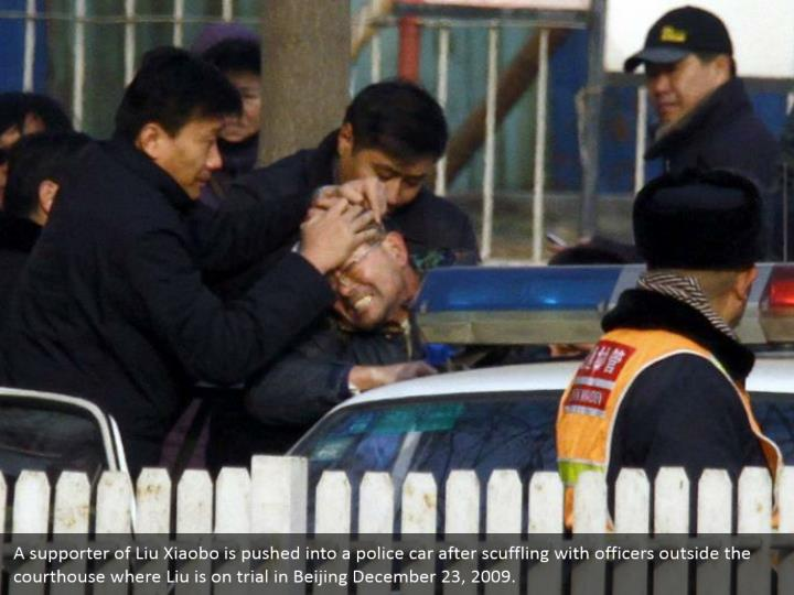 A supporter of Liu Xiaobo is pushed into a police car after scuffling with officers outside the courthouse where Liu is on trial in Beijing December 23, 2009.