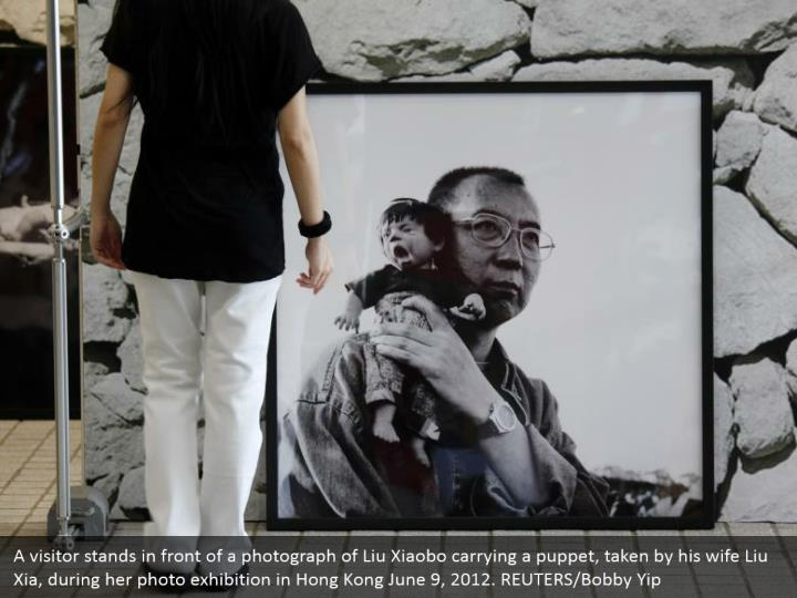 A visitor stands in front of a photograph of Liu Xiaobo carrying a puppet, taken by his wife Liu Xia, during her photo exhibition in Hong Kong June 9, 2012. REUTERS/Bobby Yip