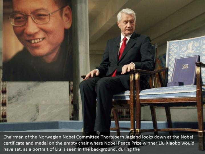 Chairman of the Norwegian Nobel Committee Thorbjoern Jagland looks down at the Nobel certificate and medal on the empty chair where Nobel Peace Prize winner Liu Xiaobo would have sat, as a portrait of Liu is seen in the background, during the