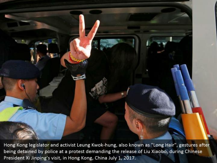 "Hong Kong legislator and activist Leung Kwok-hung, also known as ""Long Hair"", gestures after being detained by police at a protest demanding the release of Liu Xiaobo, during Chinese President Xi Jinping's visit, in Hong Kong, China July 1, 2017."