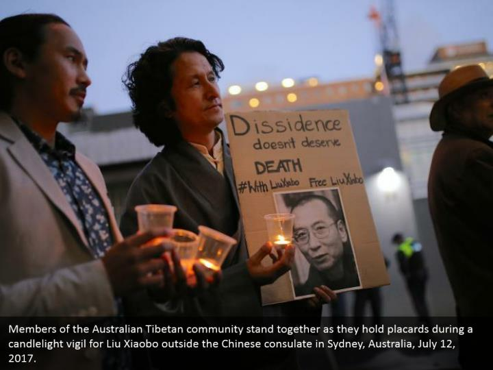 Members of the Australian Tibetan community stand together as they hold placards during a candlelight vigil for Liu Xiaobo outside the Chinese consulate in Sydney, Australia, July 12, 2017.