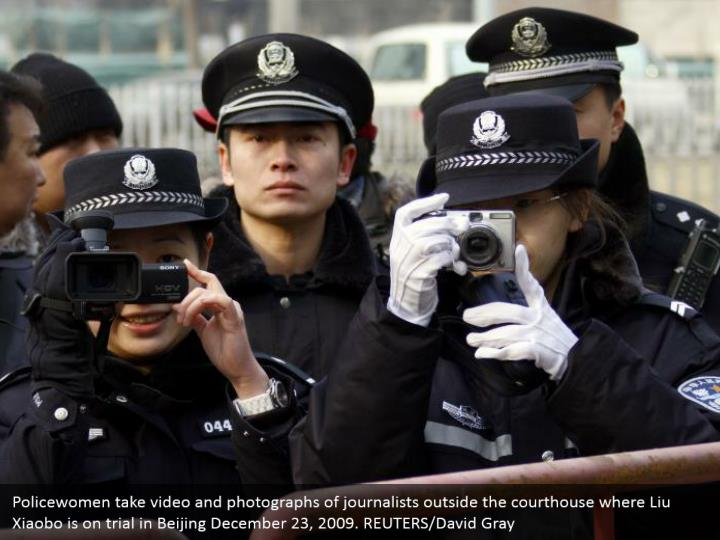 Policewomen take video and photographs of journalists outside the courthouse where Liu Xiaobo is on trial in Beijing December 23, 2009. REUTERS/David Gray