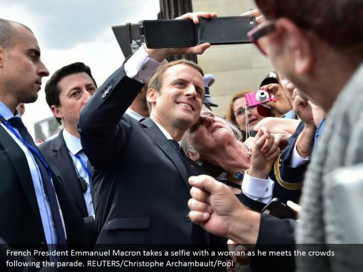 French President Emmanuel Macron takes a selfie with a woman as he meets the crowds following the parade. REUTERS/Christophe Archambault/Pool