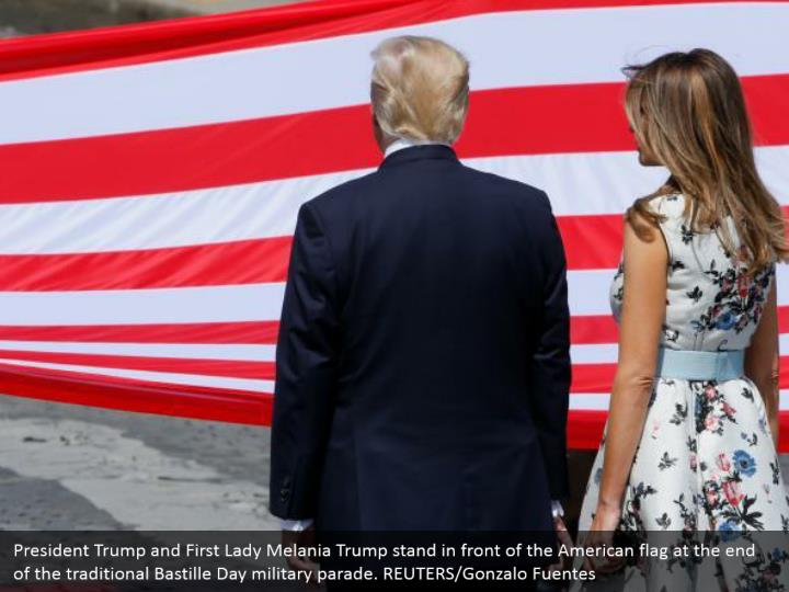 President Trump and First Lady Melania Trump stand in front of the American flag at the end of the traditional Bastille Day military parade. REUTERS/Gonzalo Fuentes