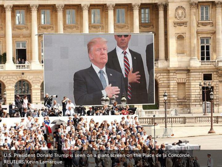 U.S. President Donald Trump is seen on a giant screen on the Place de la Concorde. REUTERS/Kevin Lamarque