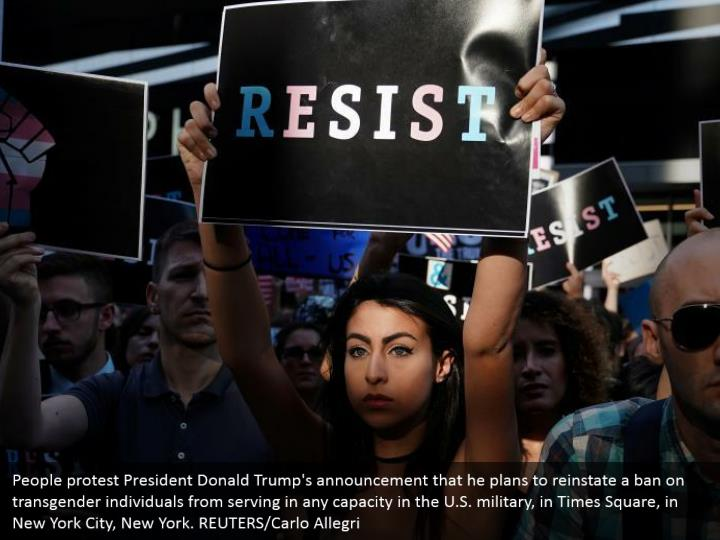 People protest President Donald Trump's announcement that he plans to reinstate a ban on transgender individuals from serving in any capacity in the U.S. military, in Times Square, in New York City, New York. REUTERS/Carlo Allegri