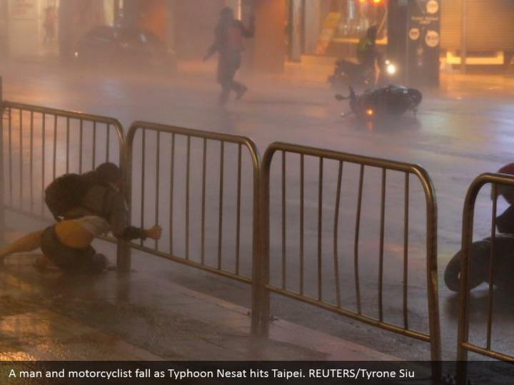 A man and motorcyclist fall as Typhoon Nesat hits Taipei. REUTERS/Tyrone Siu