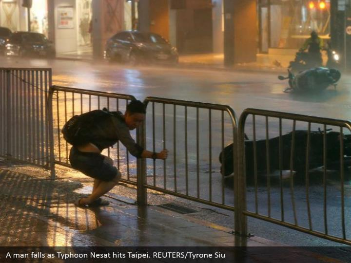 A man falls as Typhoon Nesat hits Taipei. REUTERS/Tyrone Siu
