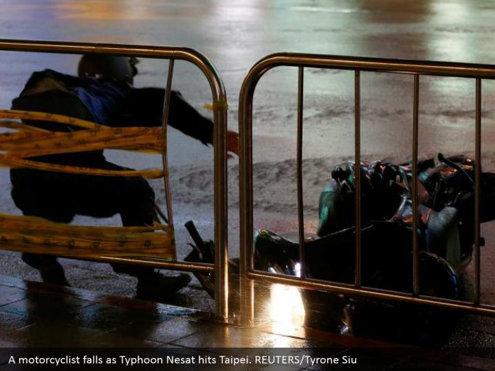 A motorcyclist falls as typhoon nesat hits taipei