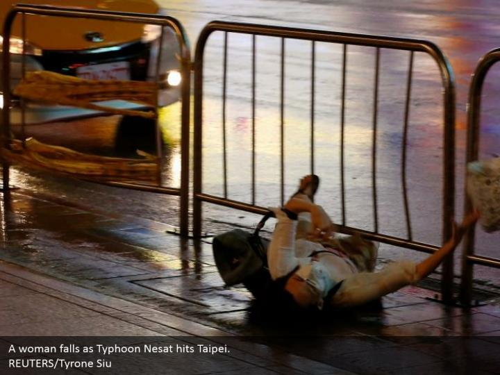 A woman falls as Typhoon Nesat hits Taipei.  REUTERS/Tyrone Siu