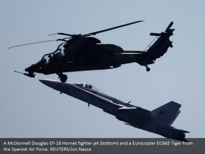 A McDonnell Douglas EF-18 Hornet fighter jet (bottom) and a Eurocopter EC665 Tiger from the Spanish Air Force. REUTERS/Jon Nazca