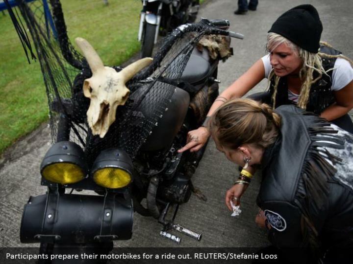 Participants prepare their motorbikes for a ride out. REUTERS/Stefanie Loos