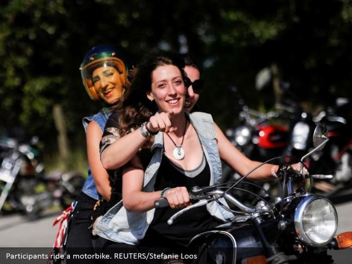 Participants ride a motorbike. REUTERS/Stefanie Loos