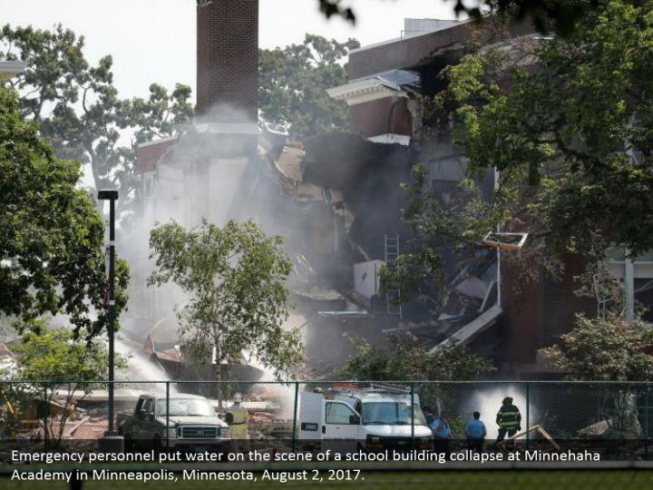 Emergency personnel put water on the scene of a school building collapse at Minnehaha Academy in Minneapolis, Minnesota, August 2, 2017.