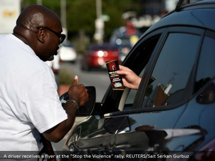 "A driver receives a flyer at the ""Stop the Violence"" rally. REUTERS/Sait Serkan Gurbuz"