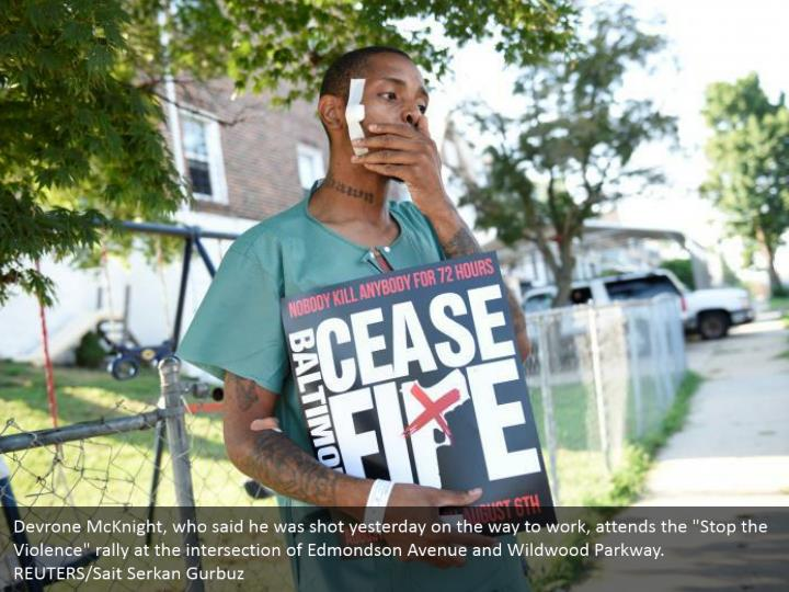"Devrone McKnight, who said he was shot yesterday on the way to work, attends the ""Stop the Violence"" rally at the intersection of Edmondson Avenue and Wildwood Parkway. REUTERS/Sait Serkan Gurbuz"