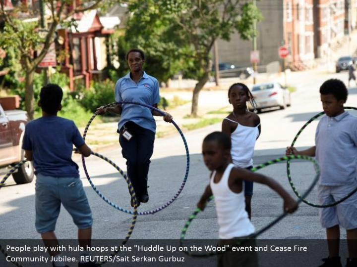 "People play with hula hoops at the ""Huddle Up on the Wood"" event and Cease Fire Community Jubilee. REUTERS/Sait Serkan Gurbuz"