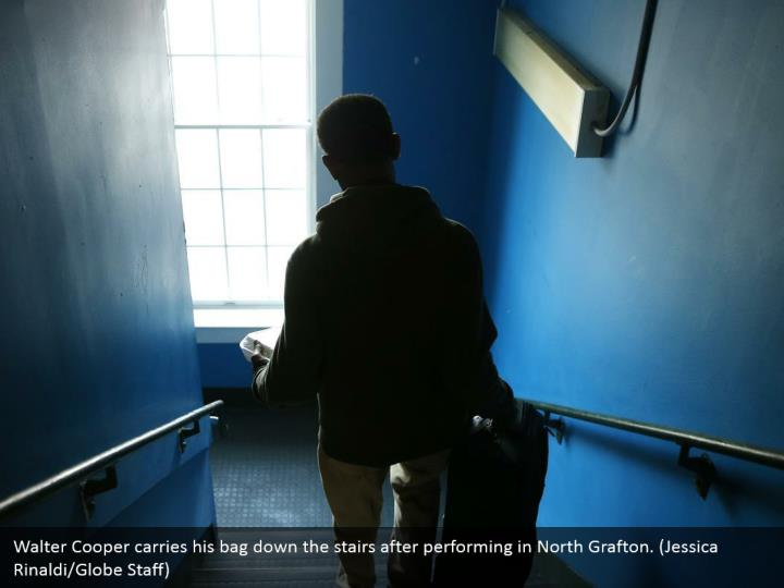 Walter Cooper carries his bag down the stairs after performing in North Grafton. (Jessica Rinaldi/Globe Staff)
