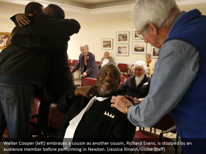 Walter Cooper (left) embraces a cousin as another cousin, Richard Evans, is stopped by an audience member before performing in Newton. (Jessica Rinaldi/Globe Staff)