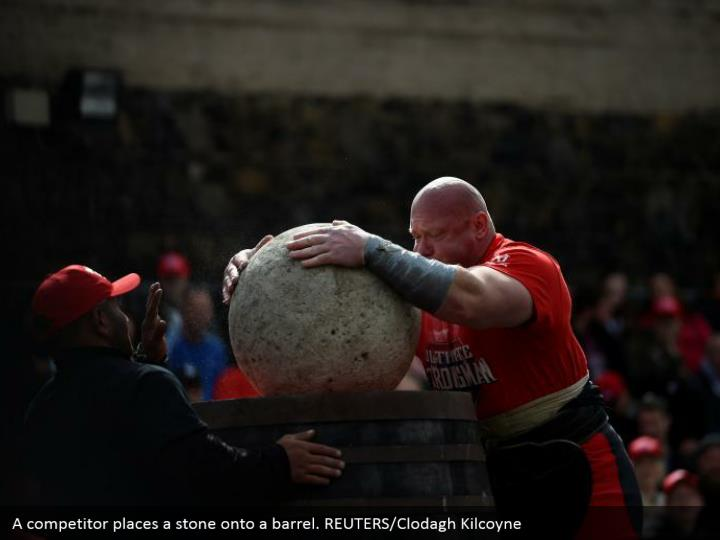 A competitor places a stone onto a barrel. REUTERS/Clodagh Kilcoyne