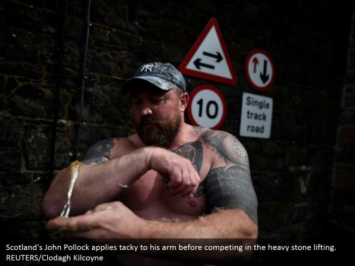 Scotland's John Pollock applies tacky to his arm before competing in the heavy stone lifting. REUTERS/Clodagh Kilcoyne