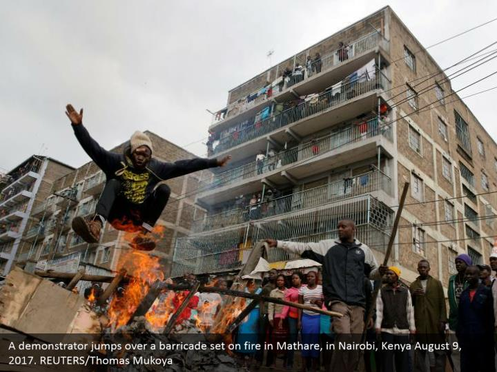 A demonstrator jumps over a barricade set on fire in Mathare, in Nairobi, Kenya August 9, 2017. REUTERS/Thomas Mukoya