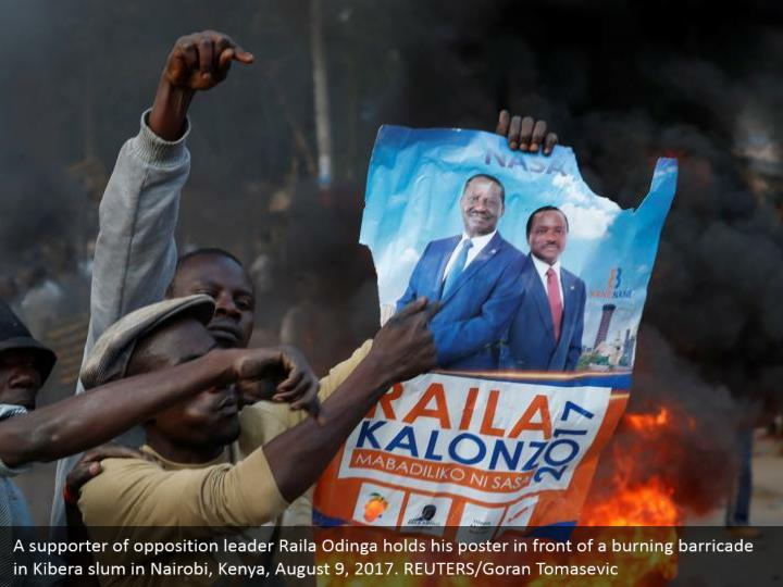 A supporter of opposition leader Raila Odinga holds his poster in front of a burning barricade in Kibera slum in Nairobi, Kenya, August 9, 2017. REUTERS/Goran Tomasevic
