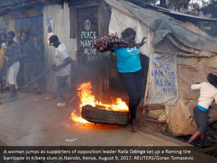 A woman jumps as supporters of opposition leader Raila Odinga set up a flaming tire barricade in Kibera slum in Nairobi, Kenya, August 9, 2017. REUTERS/Goran Tomasevic