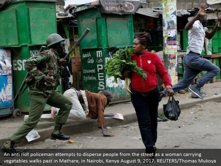 An anti riot policeman attempts to disperse people from the street as a woman carrying vegetables walks past in Mathare, in Nairobi, Kenya August 9, 2017. REUTERS/Thomas Mukoya