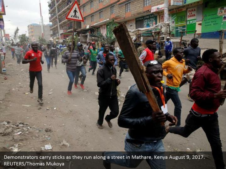 Demonstrators carry sticks as they run along a street in Mathare, Kenya August 9, 2017. REUTERS/Thomas Mukoya