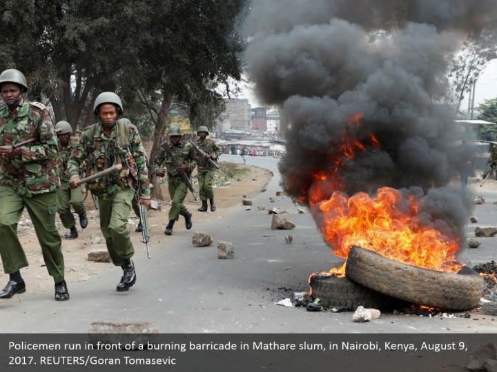 Policemen run in front of a burning barricade in Mathare slum, in Nairobi, Kenya, August 9, 2017. REUTERS/Goran Tomasevic