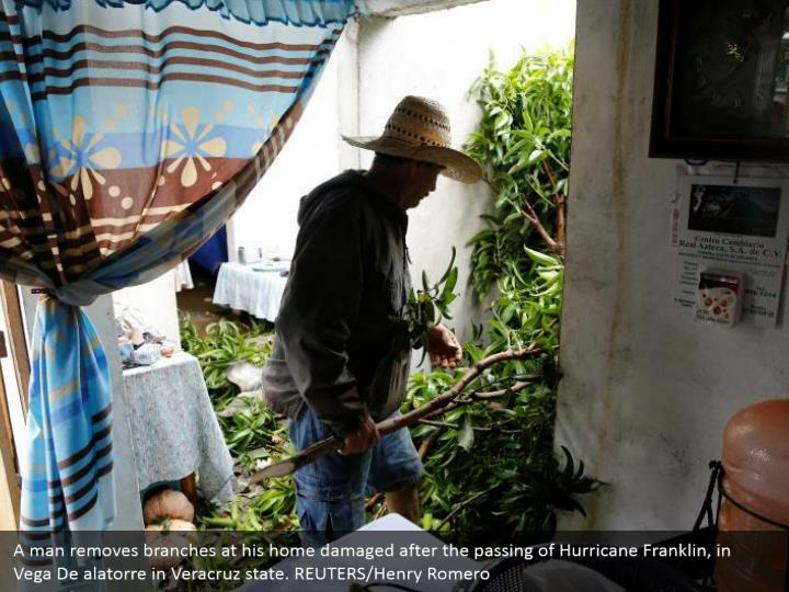A man removes branches at his home damaged after the passing of Hurricane Franklin, in Vega De alatorre in Veracruz state. REUTERS/Henry Romero