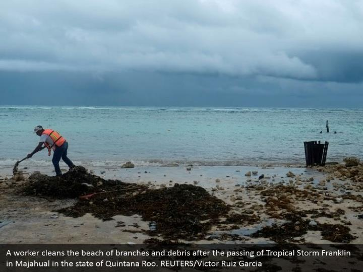 A worker cleans the beach of branches and debris after the passing of Tropical Storm Franklin in Majahual in the state of Quintana Roo. REUTERS/Victor Ruiz Garcia