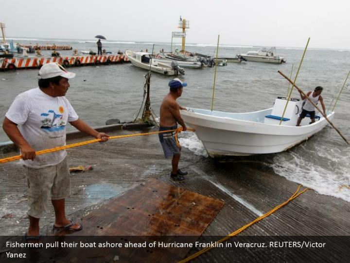 Fishermen pull their boat ashore ahead of Hurricane Franklin in Veracruz. REUTERS/Victor Yanez